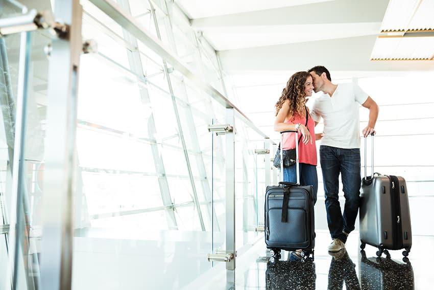 גבר לוחש באוזן לאישה. הם מחזיקים מזוודות