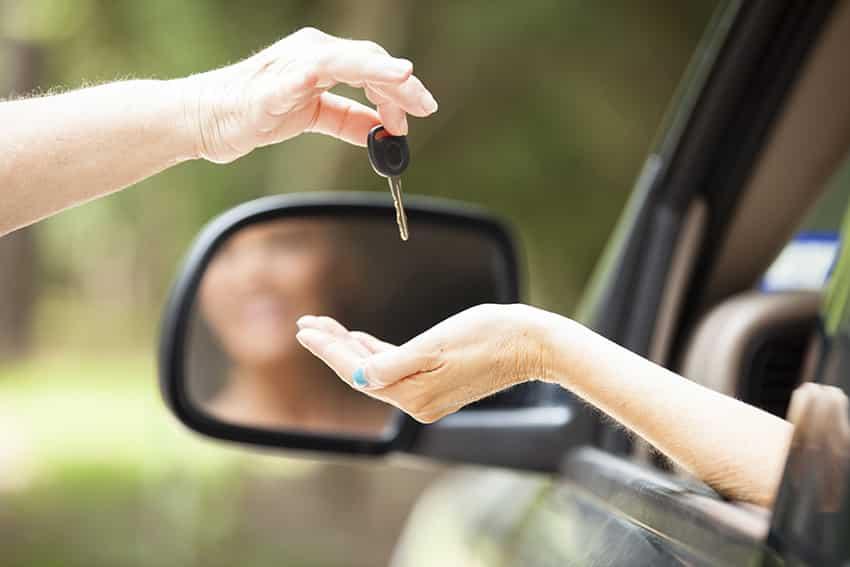 יד מושיטה מפתח לרכב לצעירה שיושבת ברכב