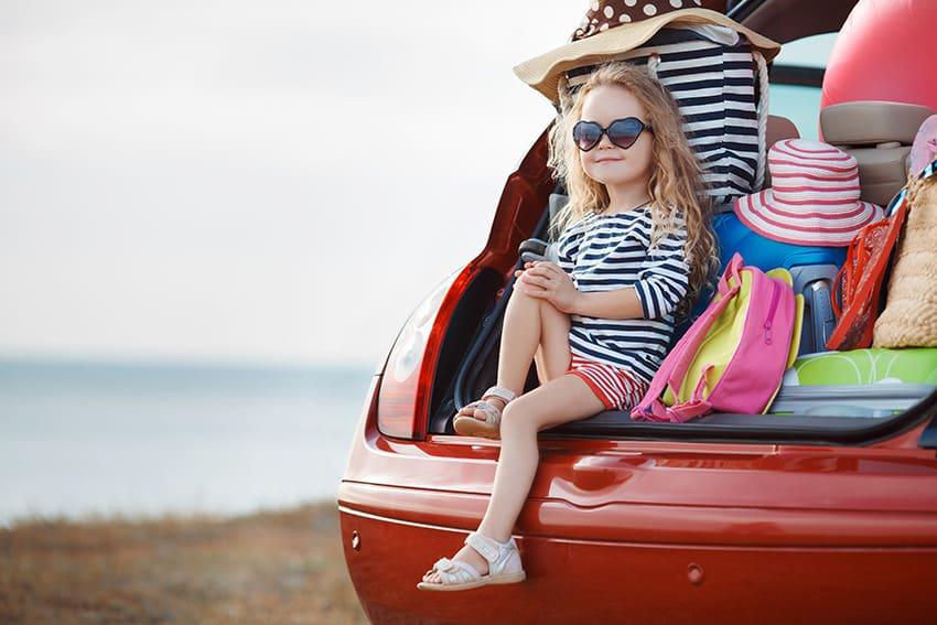 ילדה מרכיבה משקפי שמש ויושבת ותא מטען גדול