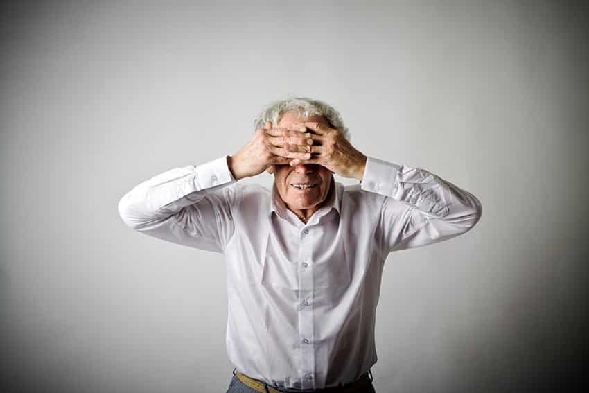 איש מבוגר שם ידיים על העיניים