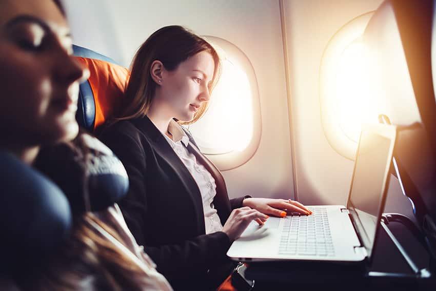 אישה יושבת במטוס ועובדת