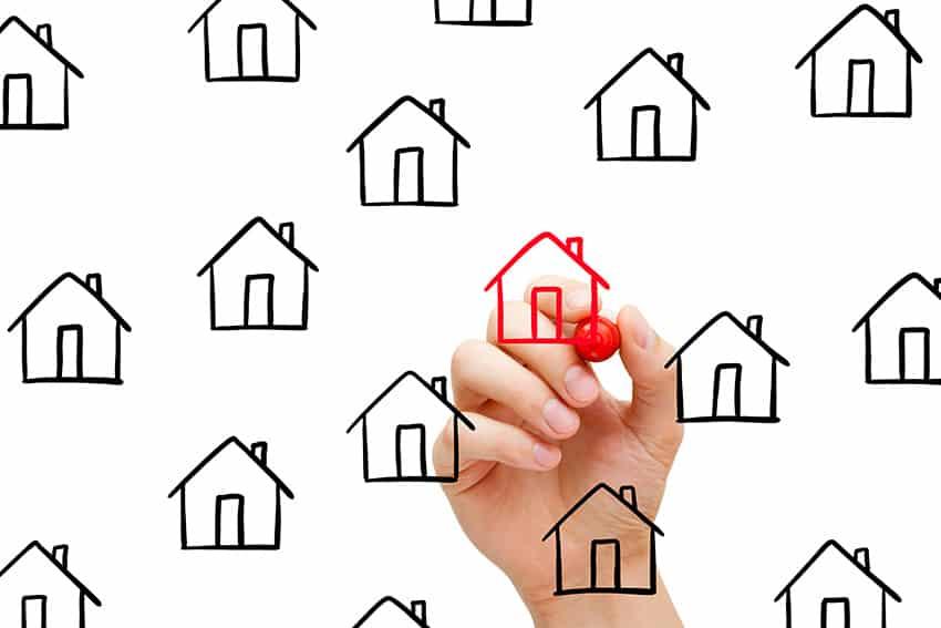 יד מציירת בית אדום ליד בתים שחורים