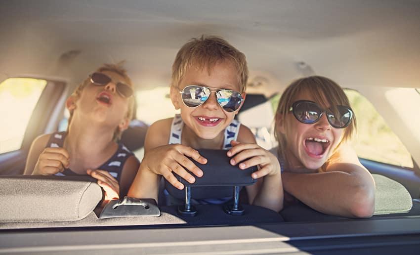 ילדים צעירים שמחים במושב האחורי של האוטו