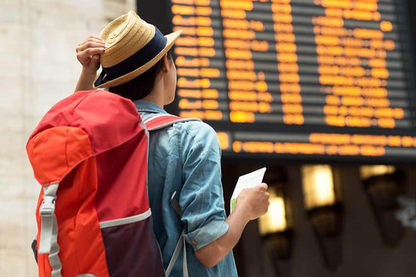 צעירה עם תרמיל אדום מסתכלת על לוח טיסות בשדה תעופה