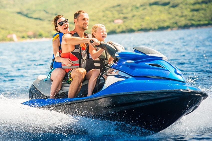 ילדה והורים רוכבים על אופנוע ים כחול