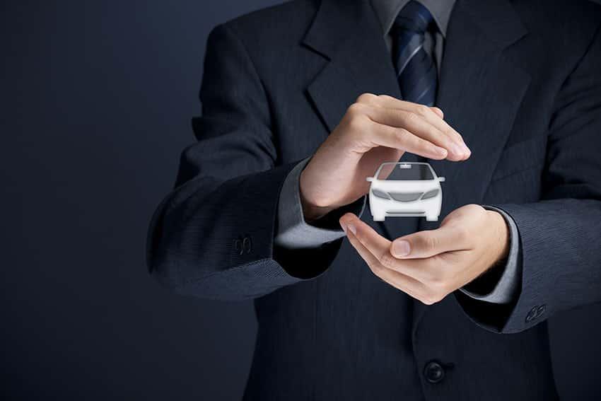 סוכן ביטוח מגן בידיו על רכב לבן