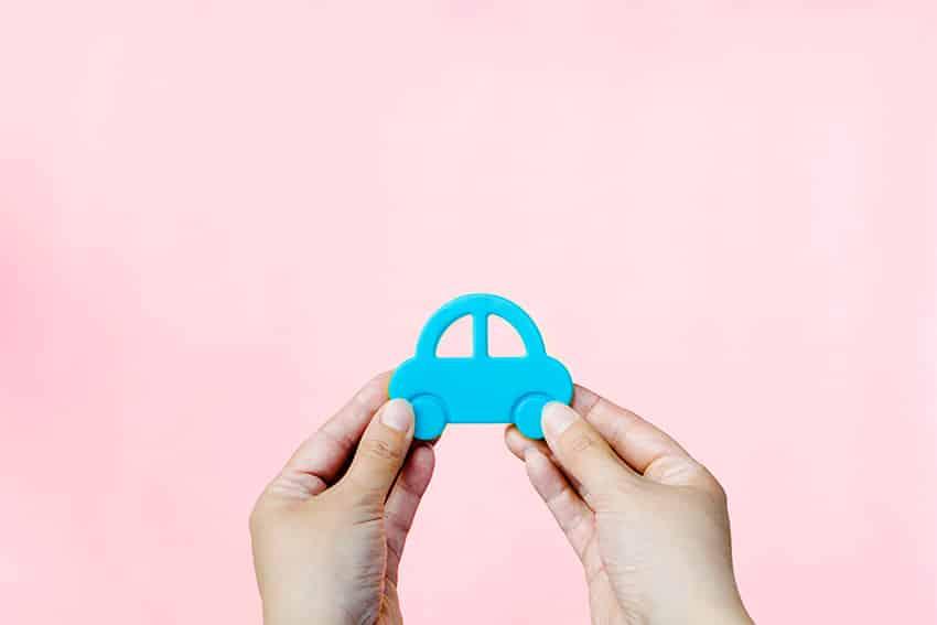 ידיים אוחזות מכונית בצבע תכלת על רקע ורוד