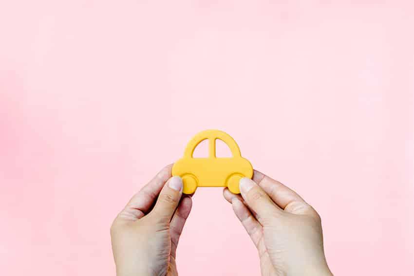 ידיים אוחזות מכונית צהובה על רקע ורוד