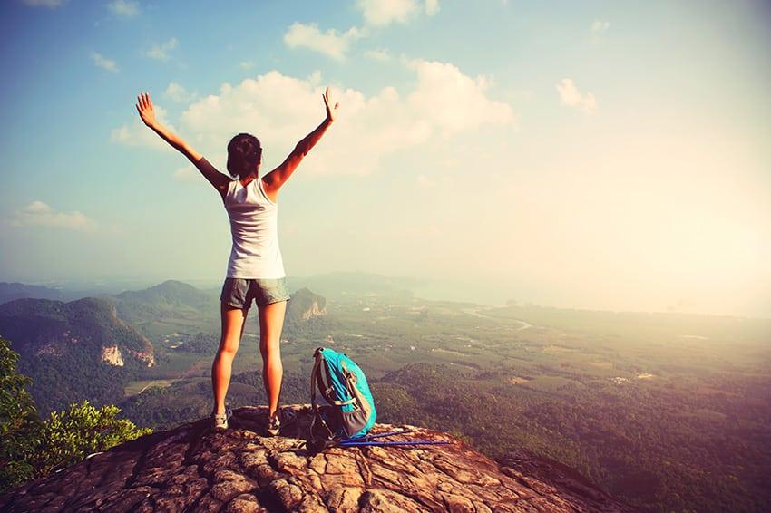 אישה בתנועת וי על פסגת הר