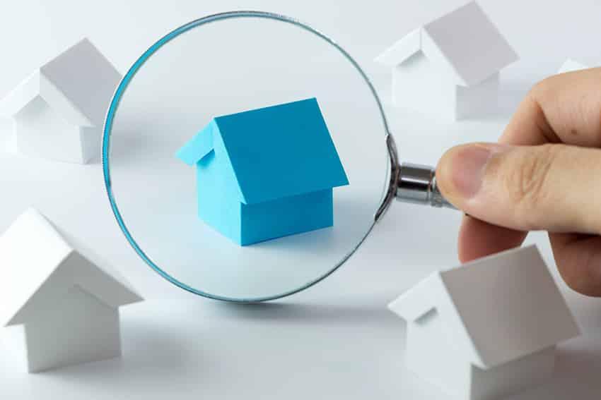 זכוכית מגדלת על מודל כחול של בית