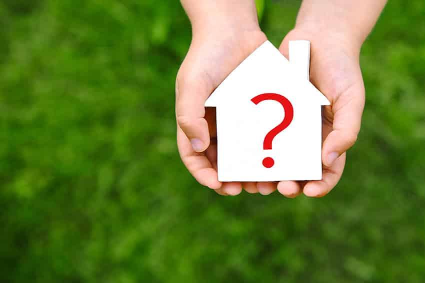 ידיים מחזיקות בית לבן עם סימן שאלה אדום מצויר עליו