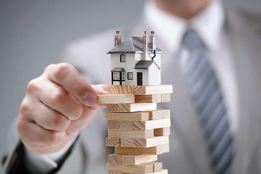 איש שומר על בית מעל מגדל קוביות
