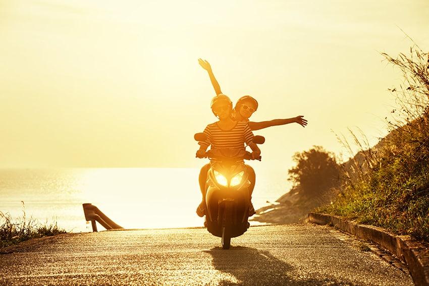 זוג רוכב על אופנוע על רקע השקיעה