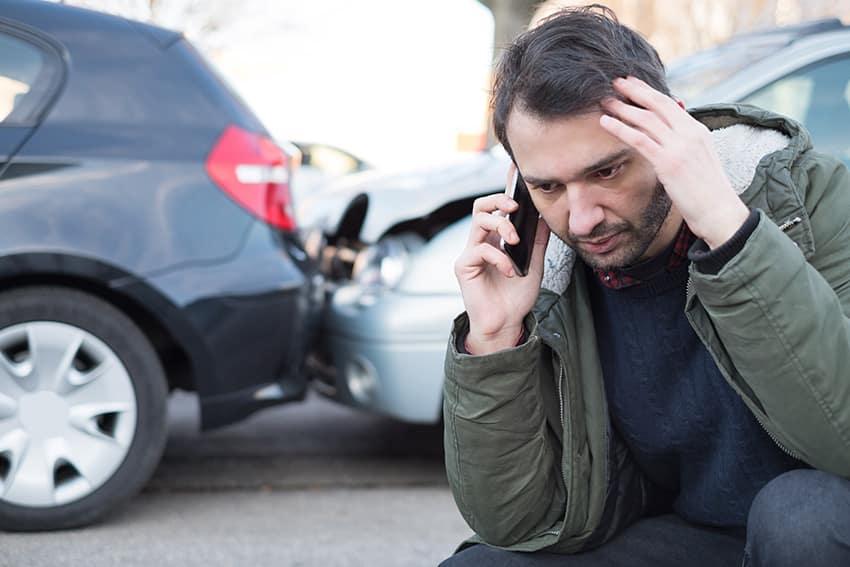 האיש קורא לעזרה ראשונה לאחר תאונה המכונית התרסקות