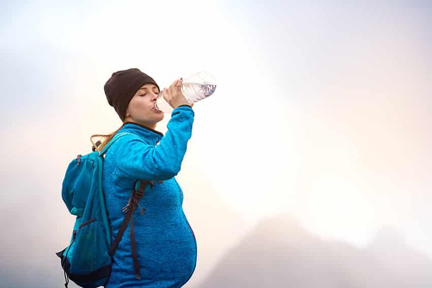 אישה בהיריון שותה מים בטיול