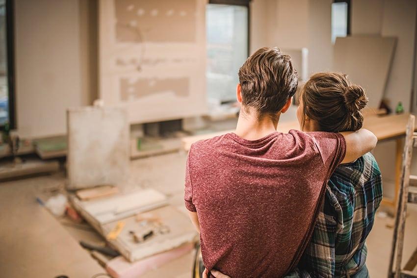 גבר מחבק אשה והם מביטים על דירה בשיפוץ