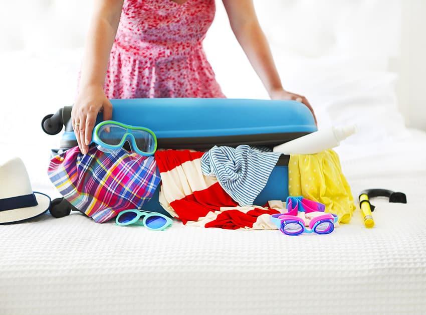 אישה מנסה לסגור מזוודה עמוסה בבגדים
