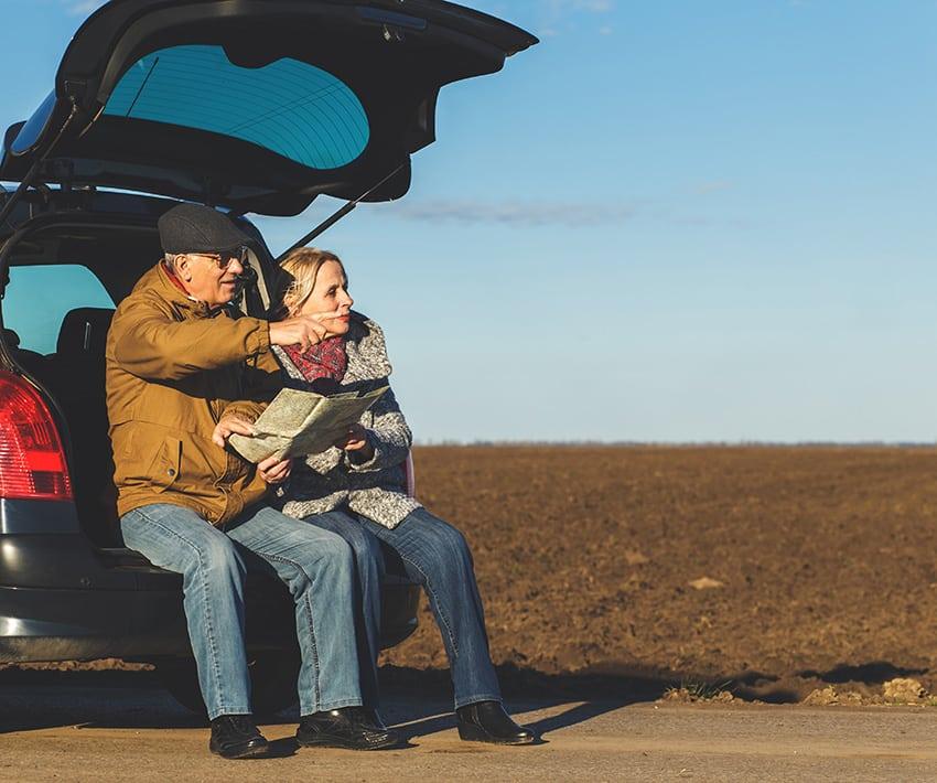 זוג מבוגר יושב על תא מטען של רכב