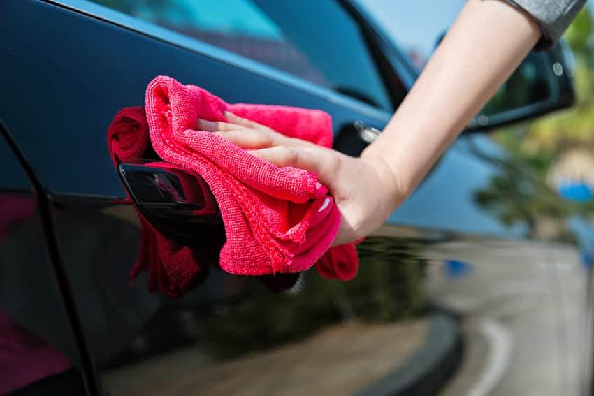 אשה מנגבת אוטו שחור במגבת אדומה