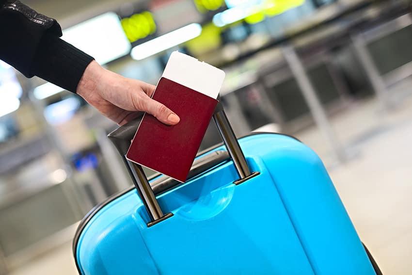 יד מחזיקה בדרכון אדום ומזוודה כחולה