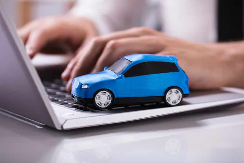 רכב צעצוע כחול על מחשב נייד