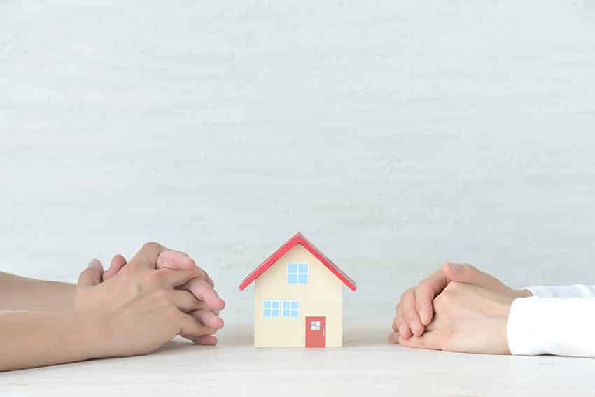 זוג ידיים זו מול זו וביניהן בית